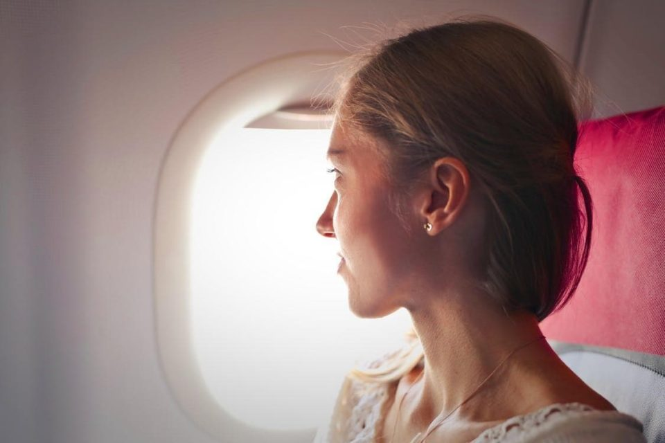 A woman looking outside the plane from a window seat