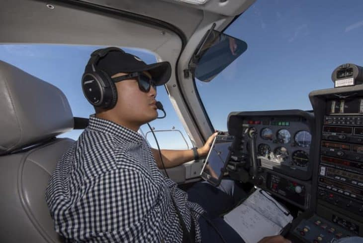 Pilot with iPad and Kneeboard in flight