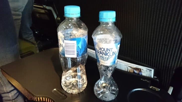 An empty bottle, sealed at 37,000ft, is crushed on descent to sea level, compared with one in its original state.