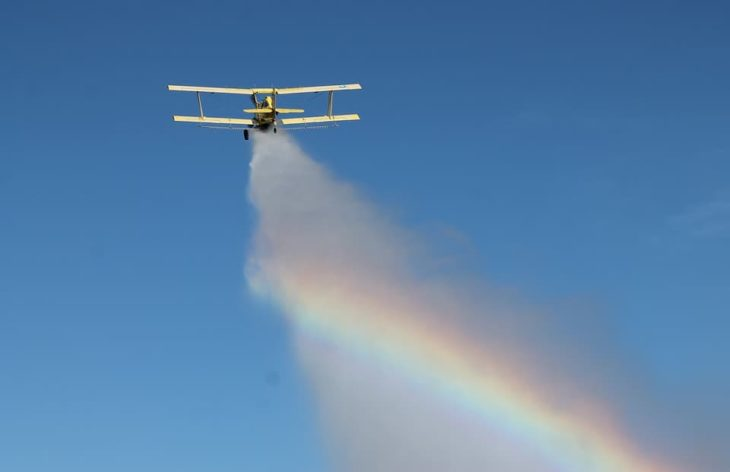 Crop Duster Dumping Water Creating Rainbow