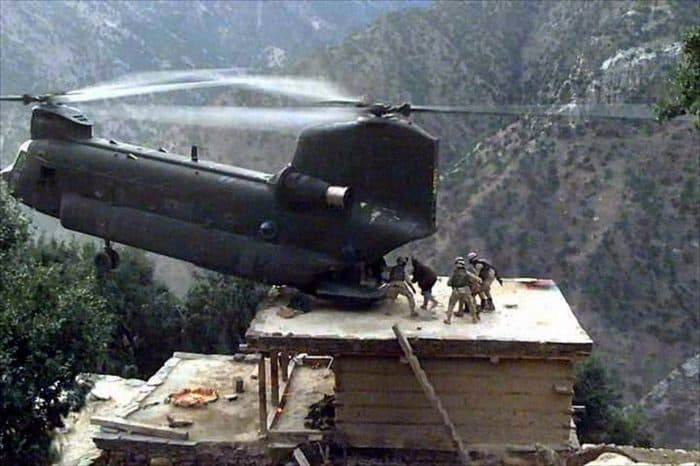 Troops being lifted of a roof in mountainous region