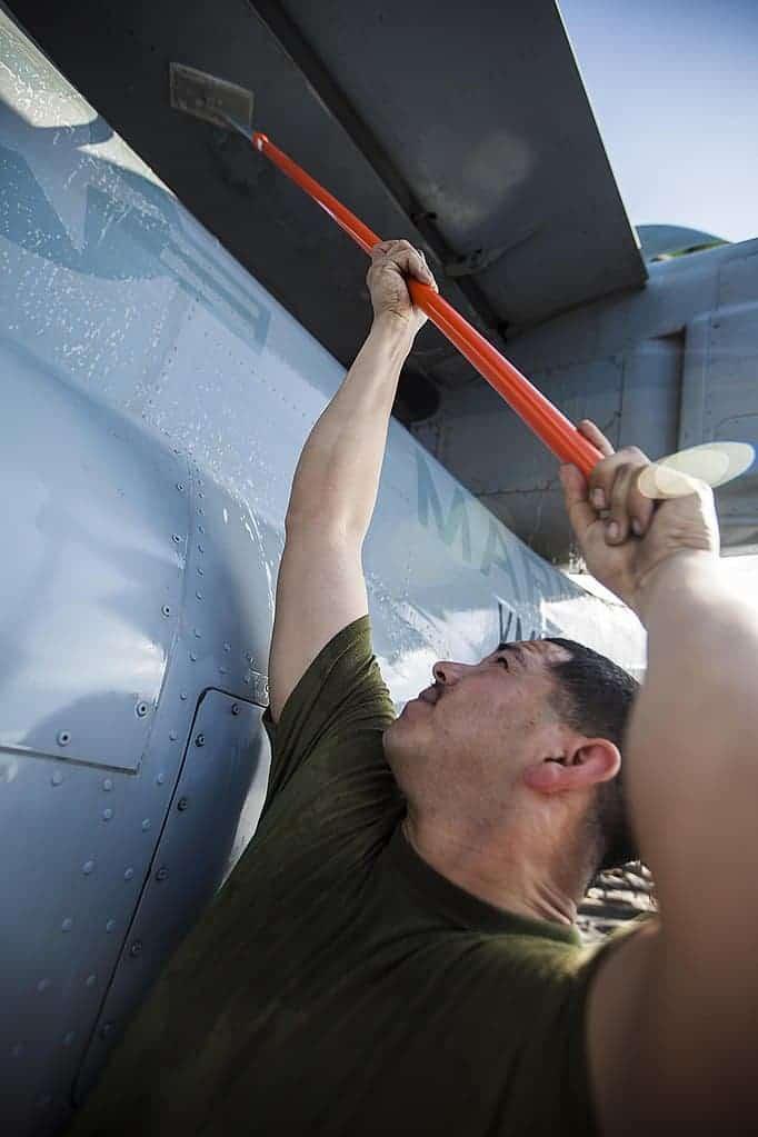 scrubbing an MV-22 Osprey aircraft on the flight deck of the USS Bataan