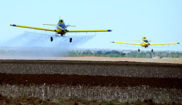 Two Air Tractor Model 502 aircraft fly eight to 10 feet off the ground to spray local fields copy