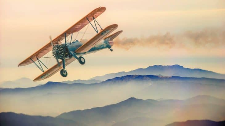Biplane Flying Low Over Mountains