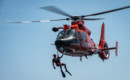 A U.S. Coast Guard USCG rescue swimmer hangs of the side of an MH 65 Dolphin