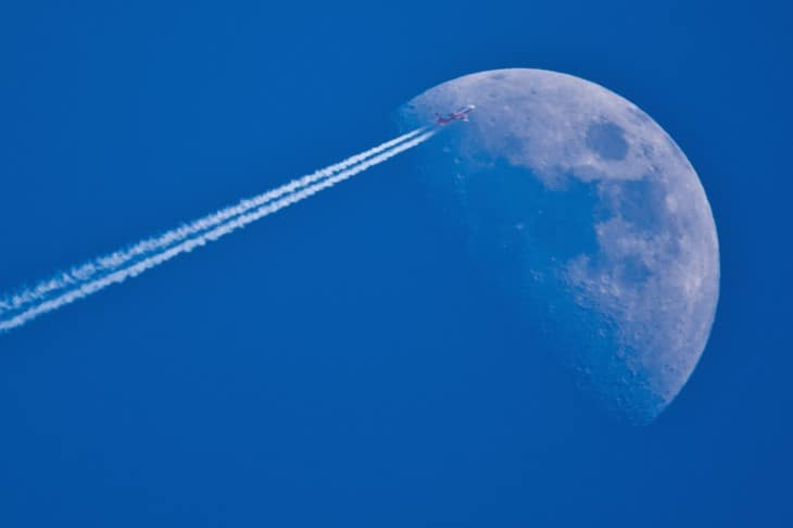 An airliner leaves contrails as it passes the Moon