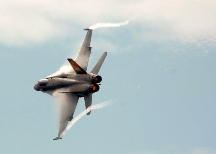 FA18 in flight with aerodynamic contrails