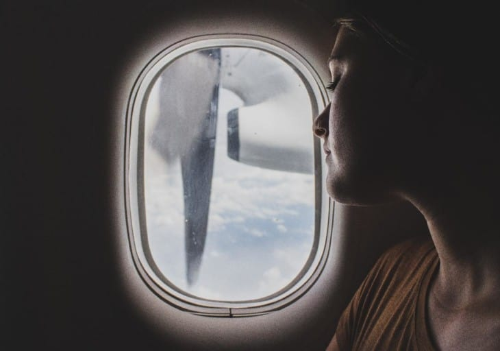 Girl looking out airplane window