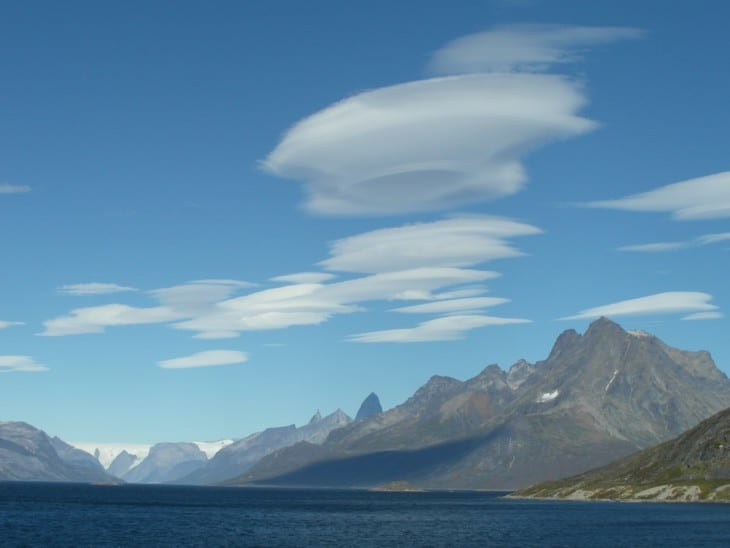 Standing lenticular clouds over a mountain ridge