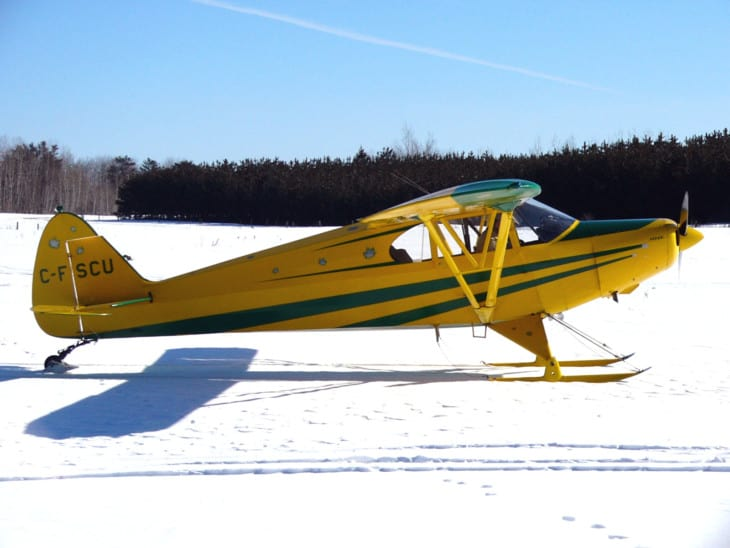 A Piper PA 12 Super Cruiser on skis.