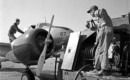 Ground crew using a fuel truck with a neoprene hose to refuel a Curtiss Wright AT 9A.