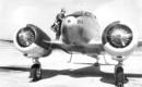 Pilot standing atop a Curtiss Wright AT 9A aircraft.