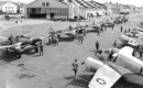U.S. Air Force pilots walking toward an aircraft hangar past a squadron of Curtiss Wright AT 9A aircraft.