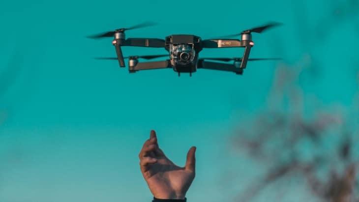 Hand reaching for DJI Mavic Pro drone
