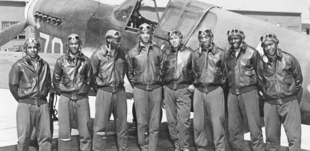 Eight Tuskegee Airmen in front of a P 40 fighter aircraft
