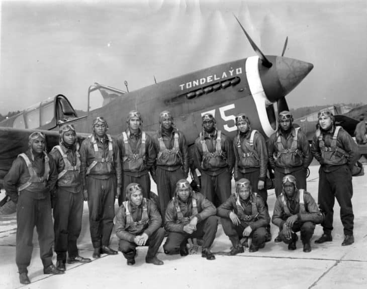 Thirteen members of Tuskegee Airmen class 43C posing in front of an airplane