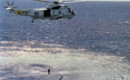 A Sikorsky SH 3H Sea King helicopter lowers an AQS 13 dipping sonar.