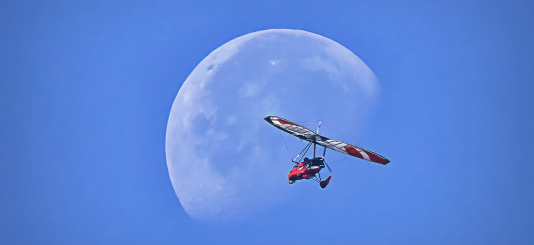 An ultralight aircraft flying in front of the moon at Wiley Slough Washington State