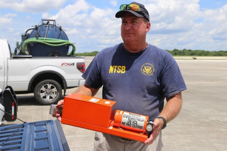 NTSB investigator Dan Boggs holds the flight data recorder recovered from the Miami Air International Boeing 737 800 that overran the runway at Naval Air Station Jacksonville