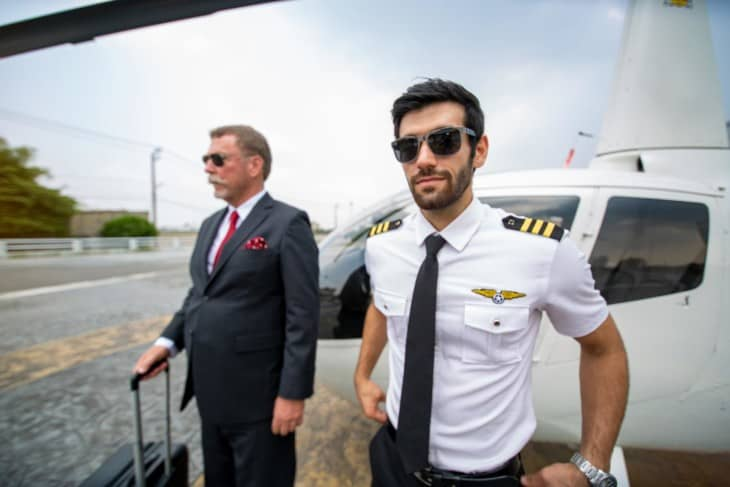 Business man and private helicopter pilot in front of helicopter