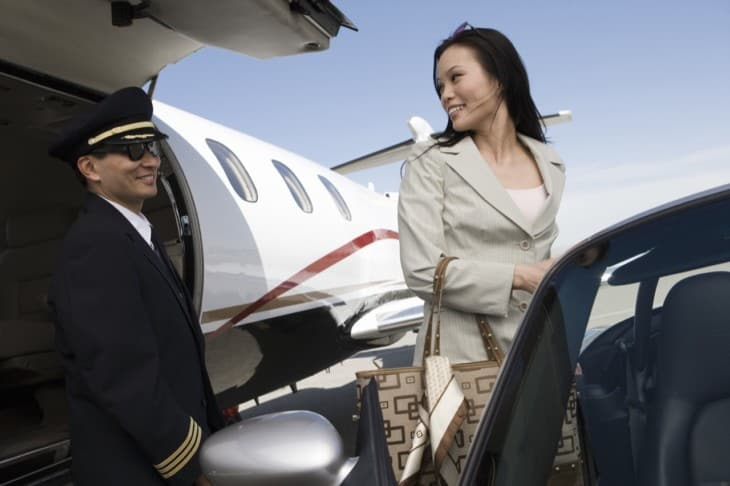 Businesswoman Looking At Airplane Pilot
