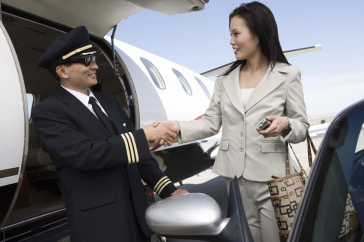 Businesswoman Shaking Hand With Pilot